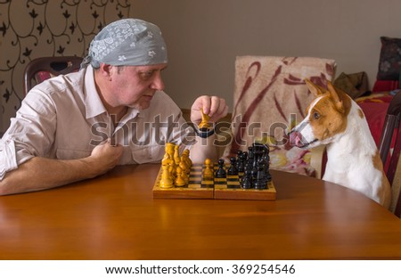 Young dog and mature man playing chess in a family tournament - stock photo