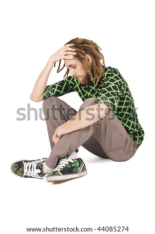 young dreadlock man sit isolated - stock photo
