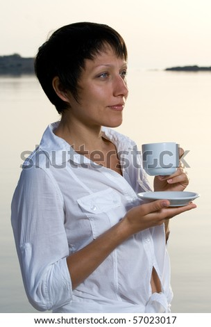 Young dressed white brunette woman meets sunrise drinking morning coffee