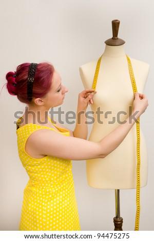 Young dressmaker in her studio - stock photo