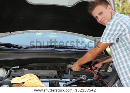 Young driver uses battery jumper cables to charge dead battery - stock photo