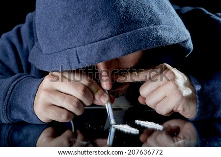 young drug addict man on hood snorting and sniffing cocaine lines on mirror with rolled banknote at home alone with moody and edgy dark studio lighting in drugs use and abuse of illegal substances - stock photo