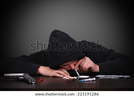 young drug addict man sniffing cocaine - stock photo