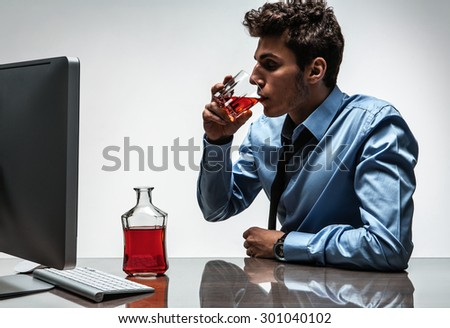 Young drunk caucasian businessman with bottle of alcohol / photo of businessman addicted to alcohol at the workplace, depression and crisis concept - stock photo
