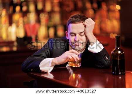 Young drunk man drinking whiskey in the bar - stock photo