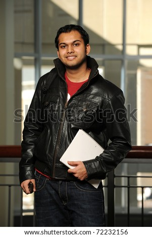 Young Eastern student holding a copybook inside a College building - stock photo
