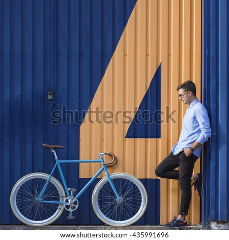 Young ecological businessman standing beside his bike - stock photo