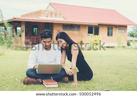 Young education couple was reading in the outdoors and good weather. And they're happy, Lifestyle concept.