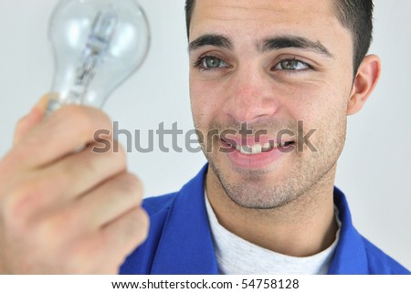 Young electrician holding a light bulb