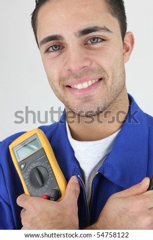 Young electrician holding a multimeter on white background