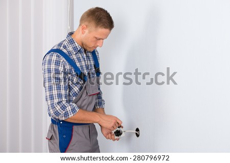 Young Electrician Installing Electrical Socket On Wall In House - stock photo