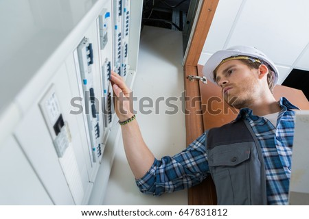 young electrician working on electric panel