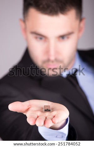 Young electronic engineer holding computer microchip. Focus on chip - stock photo