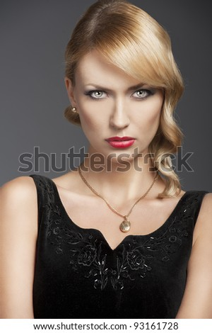 young elegant blond woman wearing black dress with an old fashion hairtyle and necklace jewellery, she is in front of the camera and looks in to the lens - stock photo