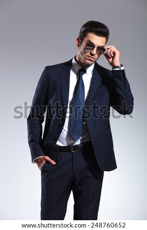 Young elegant business man taking off his sunglasses while holding one hand in his pocket. - stock photo