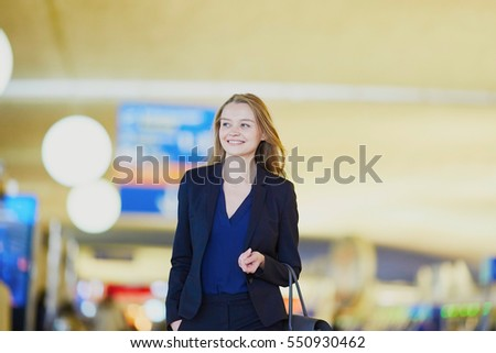 Young elegant business woman with hand luggage walking through the international airport terminal. Cabin crew member with suitcase