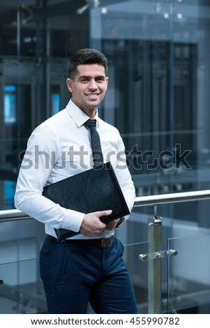 Young elegant businessman standing at the modern office corridor with his organiser and smiling