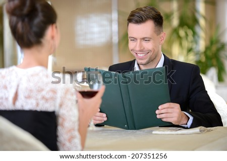 Young elegant couple drinking wine sitting in a restaurant