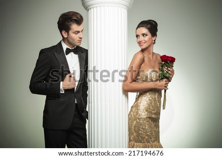 young elegant couple looking at each other near column, studio picture - stock photo