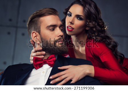 Young elegant couple portrait. Woman in red embrace man. Focus on man.