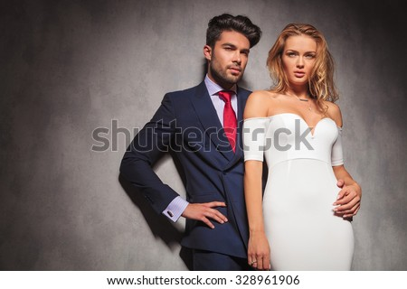 young elegant fashion couple looking away from the camera in studio, while standing with hands on hips, man holding his woman by her waist - stock photo
