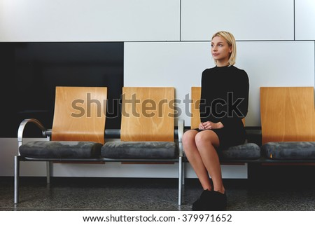 Young elegant female waiting her turn for interview with employer while sitting alone in office hallway, beautiful businesswoman thinking about ideas for information report before important conference - stock photo