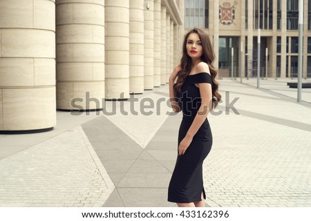 Young elegant girl posing at city street. Pretty beautiful business woman in elegant black dress against city background. - stock photo