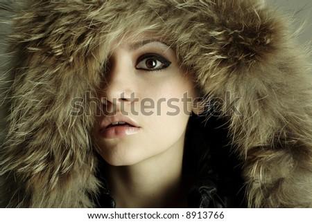 young elegant girl with fur coat. Studio portrait - stock photo