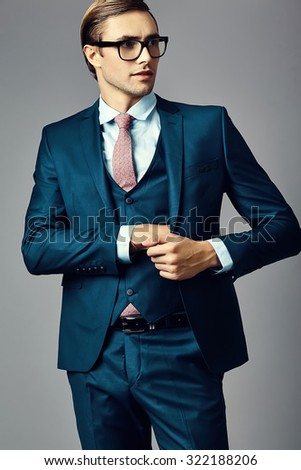 Young  elegant handsome  businessman male model in a suit and fashionable glasses, posing in studio - stock photo