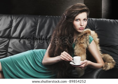young elegant lady laying down on sofa keeping and drinking from a little cup of coffee. wearing green dress.she is lying on the sofa and takes the cup with both hands. - stock photo