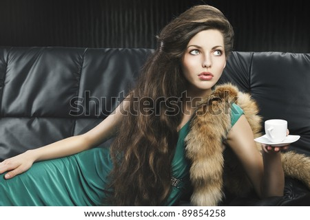young elegant lady laying down on sofa keeping and drinking from a little cup of coffee. wearing green dress. she's lying on the sofa, looks at the left and takes a cup with left hand. - stock photo