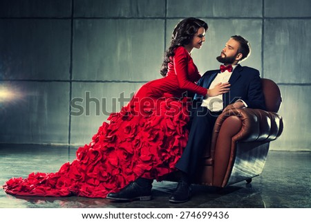 Young elegant loving couple in evening dress portrait. Woman in red and man in black suit sitting on chair. - stock photo