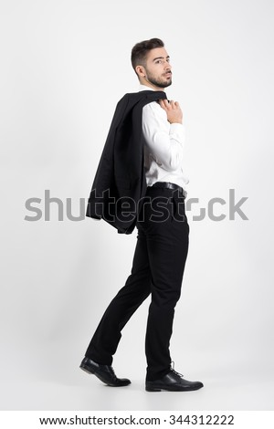 Young elegant luxurious man walking carrying tuxedo over his shoulder looking away. Full body length portrait over gray studio background. - stock photo