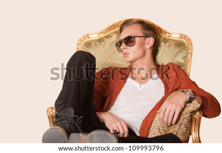 Young elegant man sitting on armchair. Isolated. - stock photo