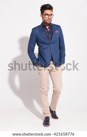 young elegant model wearing suit in walking pose looking away from the camera in studio - stock photo