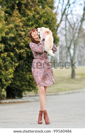 Young elegant pretty woman holding her little puppy - stock photo