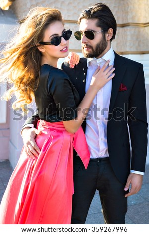 Young elegant sexy couple hugs on the street, wearing suit and glamour evening dress, enjoy their honeymoon vacation in Europe, luxury style, love, stylish lovers.