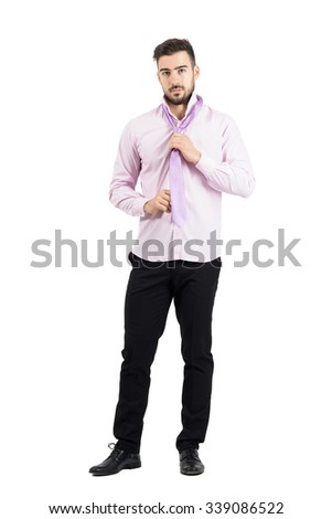 Young elegant well dressed man in pink shirt adjusting and tying pink necktie knot. Full body length portrait isolated over white studio background.  - stock photo