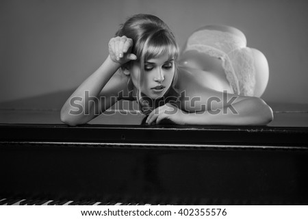 Young elegant woman in dress lying on piano in retro style interior.