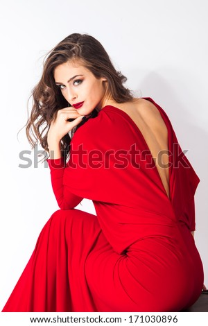 young elegant woman in red dress sit on chair studio shot - stock photo