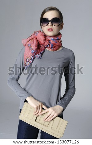 young elegant woman in sunglasses with scarf holding posing - stock photo