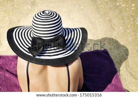 Young elegant woman wearing a black bikini top and a black and white striped beach hat sunbathing on the beach. - stock photo