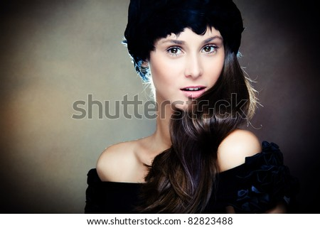 young elegant woman wearing feather hat portrait, studio shot