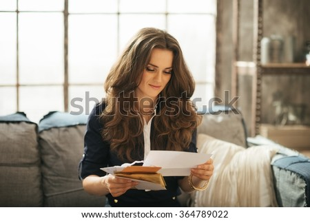 Young elegant woman with brown hairs is sitting on couch and reading correspondence in loft apartment - stock photo