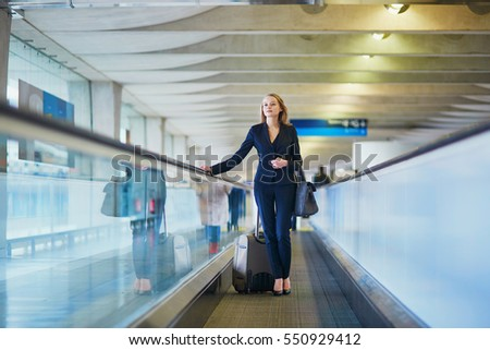 Young elegant woman with hand luggage on travelator on international airport terminal. Cabin crew member with suitcase. Travel or business trip concept