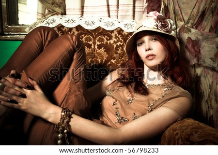 young elegant woman with hat sit in armchair, indoor shot