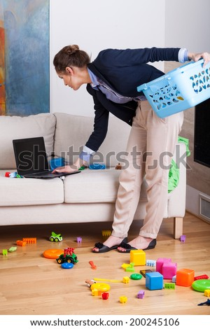Young elegant woman working on her laptop during cleaning up living room - stock photo