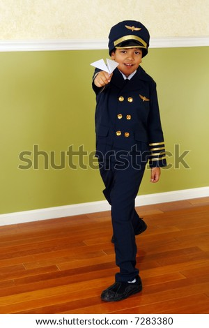 Young elementary boy in an airline pilot's uniform flying a paper airplane. - stock photo