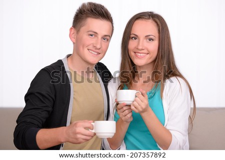 Young emotional couple drinking tea or coffee while sitting on sofa at home - stock photo