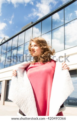 Young emotional girl with tousled hair on the background of office building
